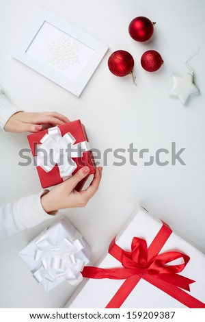 Image of giftbox held by female surrounded by other xmas presents - stock photo
