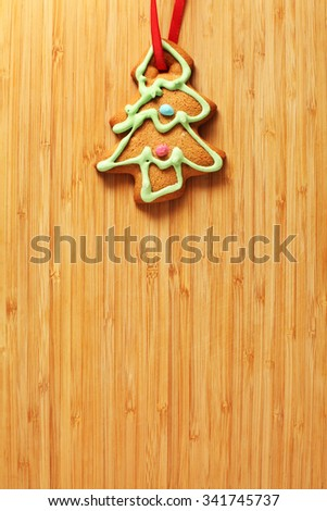 Image of gingerbread Christmas tree cookie over wooden texture - stock photo