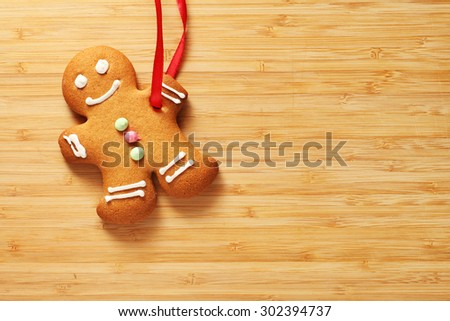 Image of Gingerbread man cookie over wooden texture with copyspace - stock photo