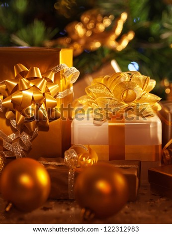 Image of golden gift boxes lying down under festive spruce tree, luxury presents, New Year party, wintertime home ornament, Christmas tree, beautiful shiny decorations, traditional celebration - stock photo