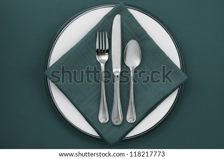 Image of green dinner setting on green background - stock photo