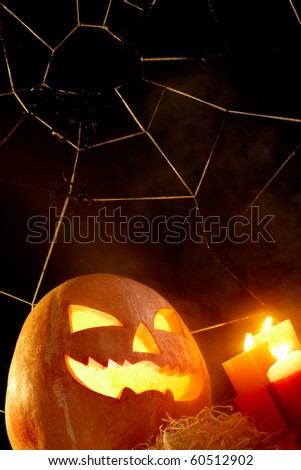 Image of Halloween pumpkin with burning candles and cobweb with spiders near by - stock photo