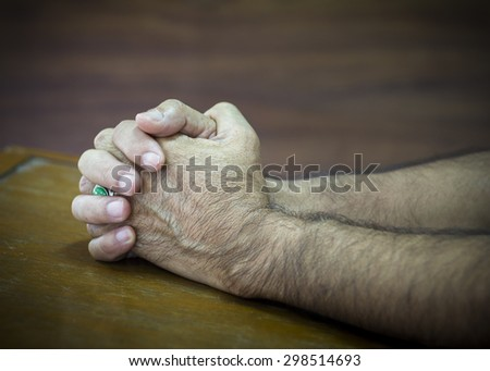 image of hands of a man praying to God on wooden background - stock photo