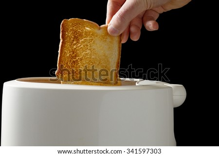 Image of Hands of a man taking fresh toast out of a toaster isolated on black background with clipping path - stock photo