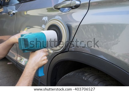Image of hands worker polish a car body with an auto polisher in the garage - stock photo