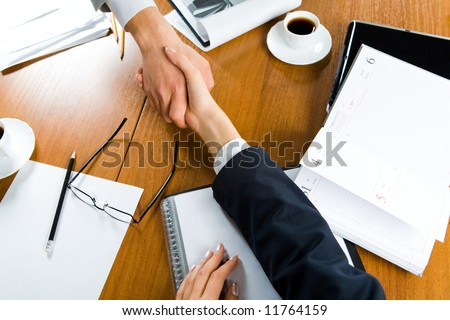 Image of handshake of partners over table with business objects on it - stock photo