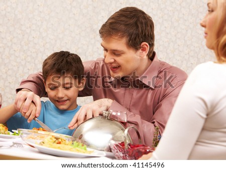 Image of handsome man showing how to cut roasted turkey to his son - stock photo