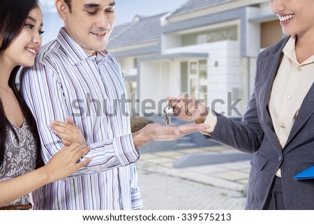 Image of happy asian couple receive keys of their new home in front of the house - stock photo