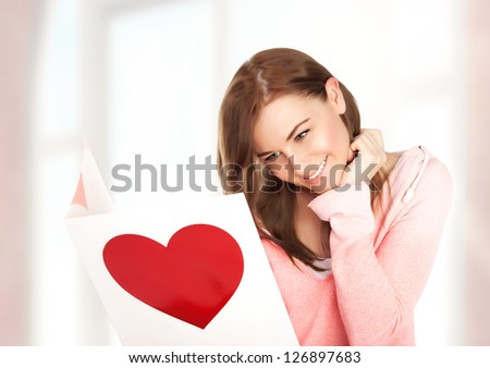 Image of happy beautiful female reading romantic postcard with big red heart, attractive brunette woman got sensual greeting card and isolated on white background, Valentine day,love concept - stock photo