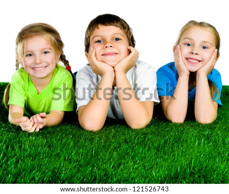 Image of happy boy and girls lying on a green grass - stock photo