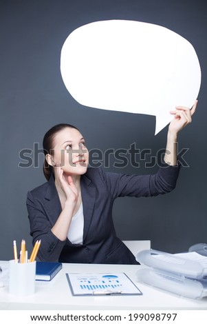 Image of happy businesswoman looking at paper speech bubble in her hand - stock photo