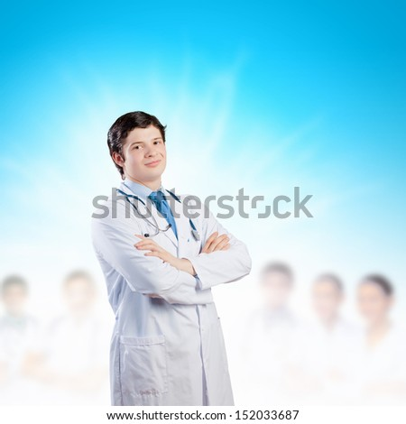 Image of happy confident doctor in uniform with colleagues at background - stock photo