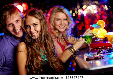 Image of happy couple looking at camera with pretty girl on background - stock photo