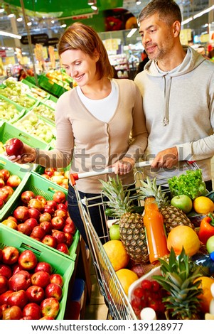 Image of happy couple with cart full of products choosing apples in supermarket - stock photo
