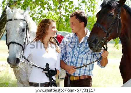 Image of happy couple with purebred horses looking at each other - stock photo