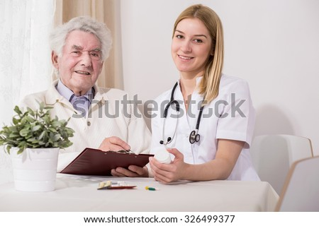 Image of happy elderly patient during medical home visit - stock photo