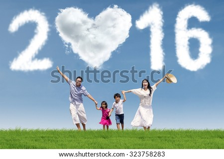 Image of happy family running at field while enjoying new year holiday under cloud shaped numbers 2016 - stock photo
