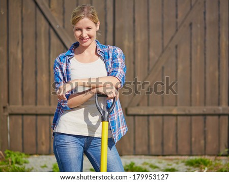 Image of happy female farmer with instrument looking at camera - stock photo