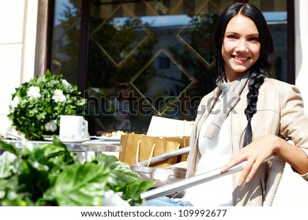Image of happy female in open air cafe looking at camera in urban environment - stock photo