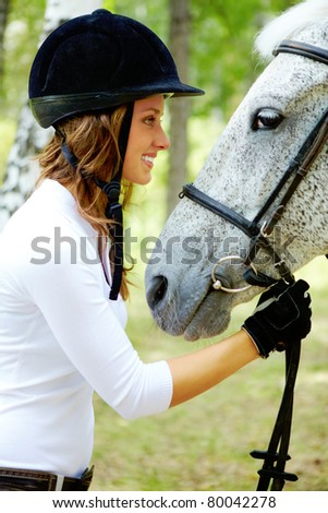 Image of happy female in riding cap holding purebred horse by bridle and looking at it - stock photo