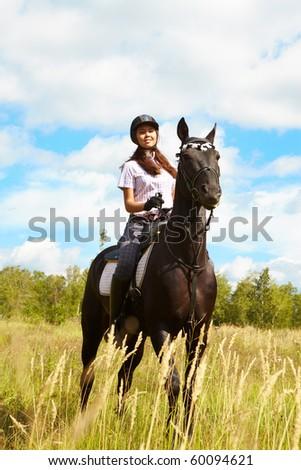 Image of happy female jockey sitting on purebred horse outdoors - stock photo