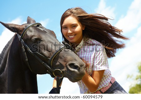 Image of happy female with black purebred horse near by outside - stock photo