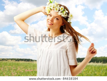 Image of happy female with floral wreath on head looking at camera - stock photo