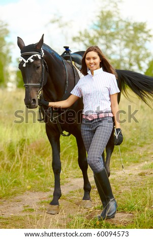 Image of happy female with purebred horse outdoors - stock photo