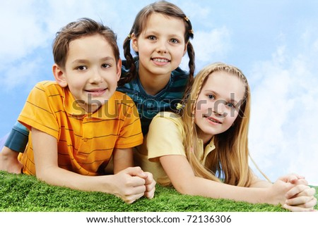 Image of happy friends lying on the grass and looking at camera - stock photo