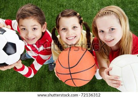 Image of happy friends on the grass with balls looking at camera - stock photo
