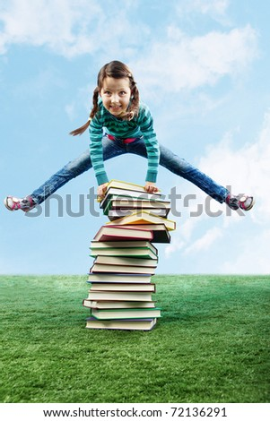 Image of happy girl jumping on the grass through stack of books - stock photo