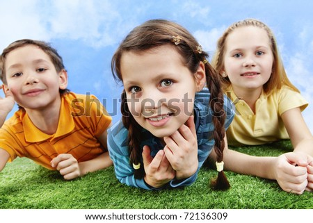 Image of happy girl lying on the grass and looking at camera with friends at background - stock photo