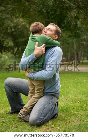 Image of happy man embracing his son in park - stock photo
