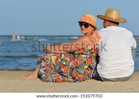 image of happy mature couple having fun relaxing sitting back to back at seashore on sandy beach summer sea outdoors background  - stock photo