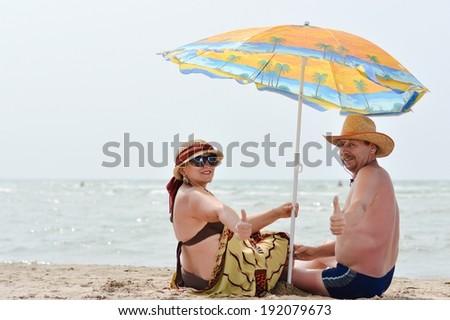 image of happy mature couple having fun sitting under sun umbrella at seashore on sandy beach summer sea outdoors background  - stock photo