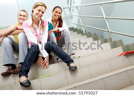 Image of happy teenagers sitting in the corridor of college and looking at camera - stock photo