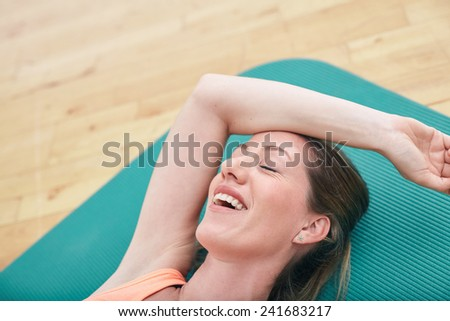 Image of happy woman resting on exercise mat smiling with her eyes closed. Fitness woman relaxing in break at gym. - stock photo
