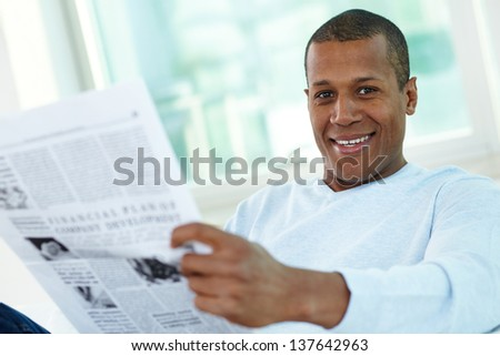 Image of happy young African man looking at camera while reading newspaper - stock photo