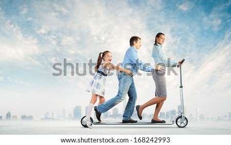 Image of happy young family riding scooter - stock photo