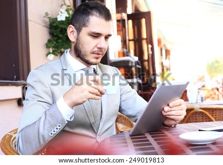 Image of happy young man using digital tablet in cafe - stock photo