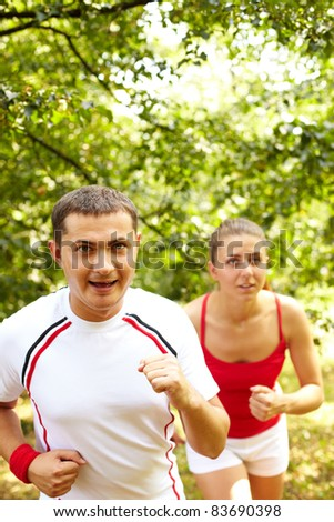 Image of happy young sportsman running with his girlfriend behind - stock photo