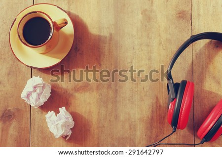image of headphones over wooden table and empty crumpled paper. top view. retro filter  - stock photo