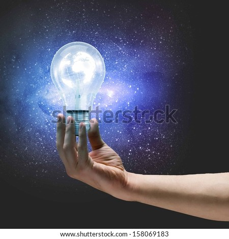 Image of human hand holding bulb with earth planet inside - stock photo