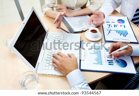 Image of human hands during work with laptop and business documents at meeting - stock photo