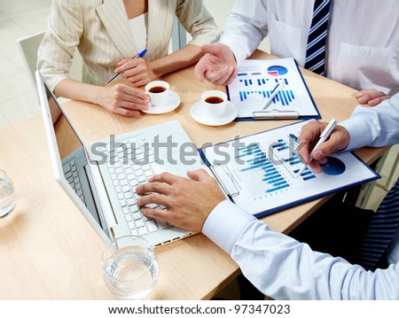 Image of human hands with business documents and laptop at meeting - stock photo