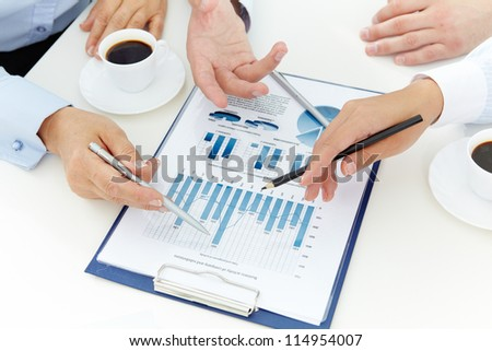 Image of human hands with pens over business document at meeting - stock photo