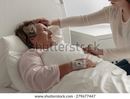 Image of ill grandma lying in hospital bed - stock photo