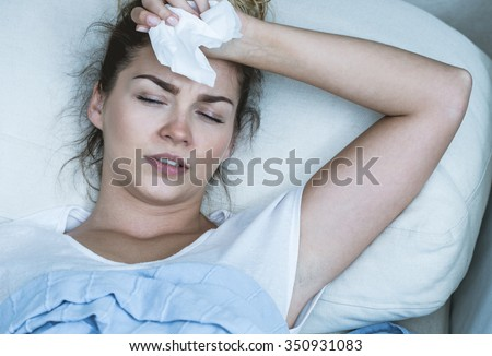 Image of ill woman with headache resting in bed - stock photo