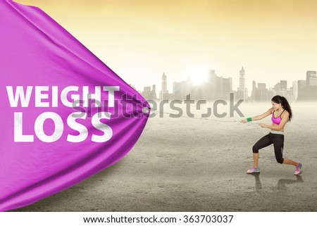 Image of indian young woman wearing sportswear and pulls weight loss text with a big flag outdoors - stock photo