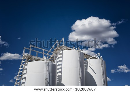 Image of industrial storage tanks against blue sky with clouds - stock photo